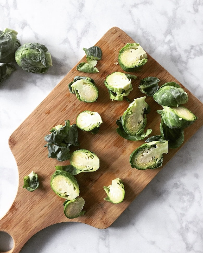 A cutting board with sliced Brussels sprouts on it.