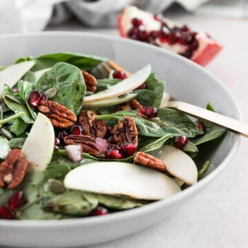 A bowl of spinach salad with fresh apples