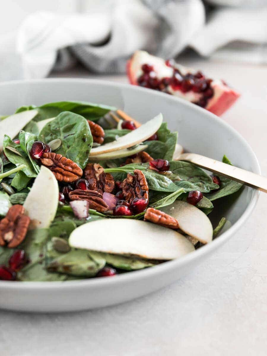 Bowl of Apple Spinach Salad with pomegranate in the background.