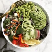 A buddha bowl with a fork and napkin.