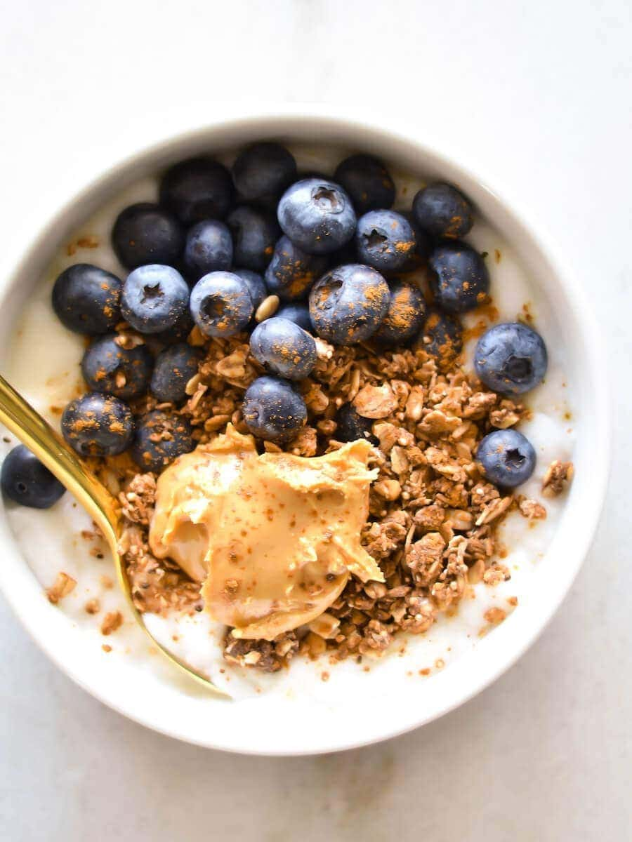 A yogurt bowl topped with granola, nut butter, and fresh blueberries.