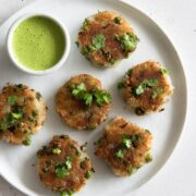 A plate of aloo tikki with a bowl of chutney