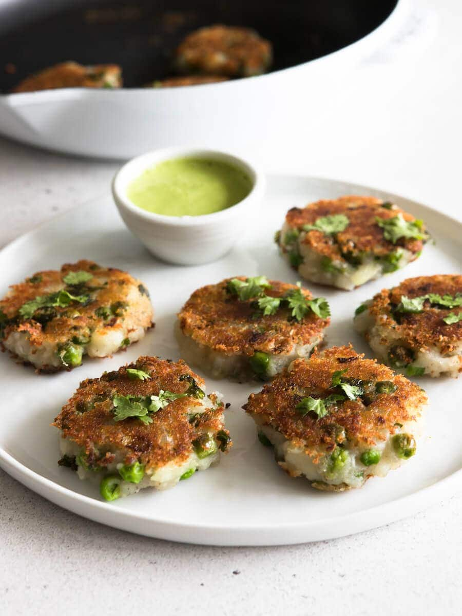 A plate of aloo tikki with a side of cilantro chutney.