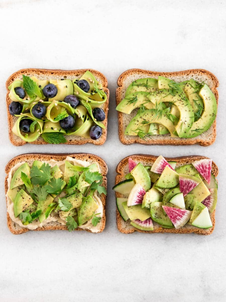 Four avocado toasts, each with different toppings.