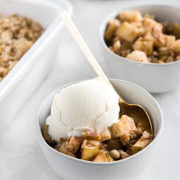 Two bowls of apple crisp, one with a scoop of ice cream