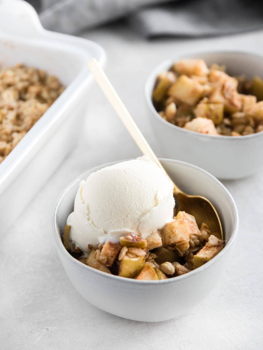 Two bowls of walnut apple crisp next to the baking dish, including one with a scoop of coconut ice cream.