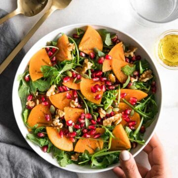 Bowl of arugula salad with persimmon