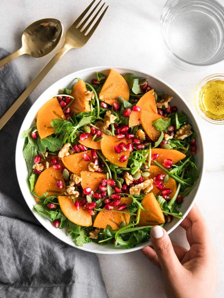 A bowl of arugula persimmon salad with dressing and a glass of water in the side.