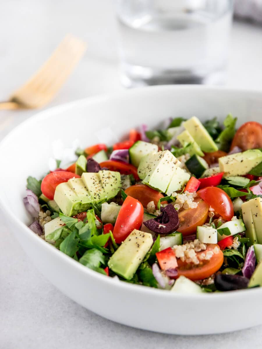 Bowl of Mediterranean Quinoa Salad with a Glass of Water