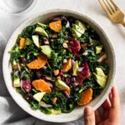 Bowl of kale citrus salad with hand