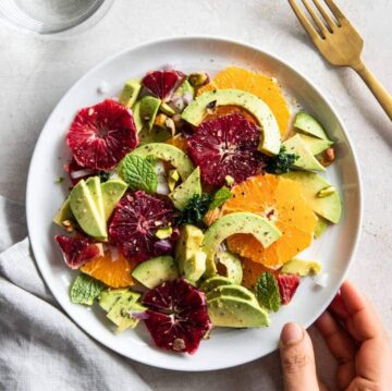 A plate of citrus and avocado salad.