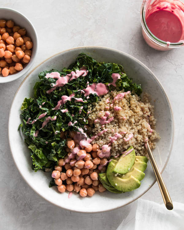 Prepared quinoa bowl with glass of dressing on the side.