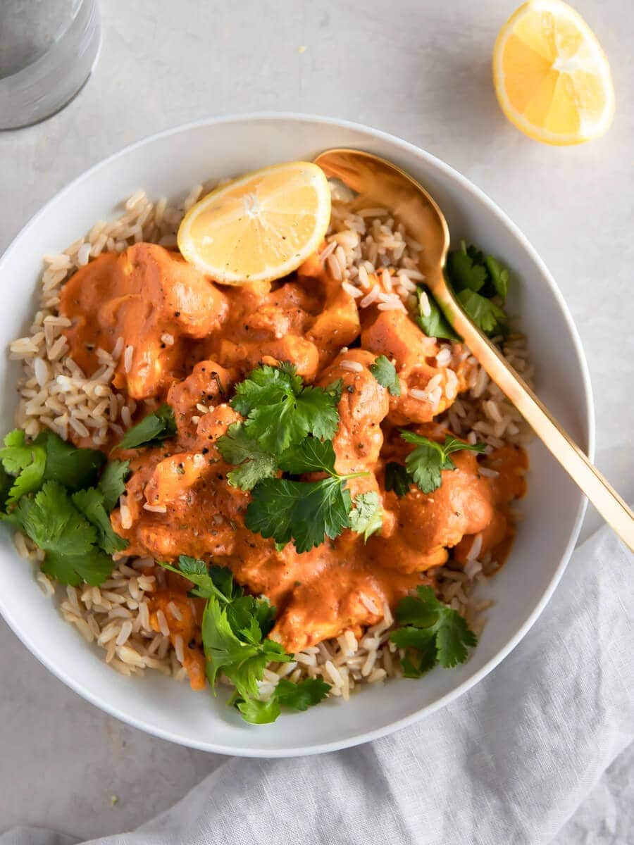 A bowl of cauliflower tikka masala served over brown rice.