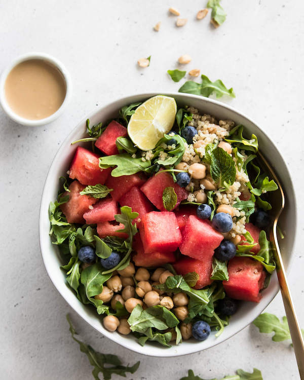 Watermelon arugula bowl with a bowl of dressing on the side.