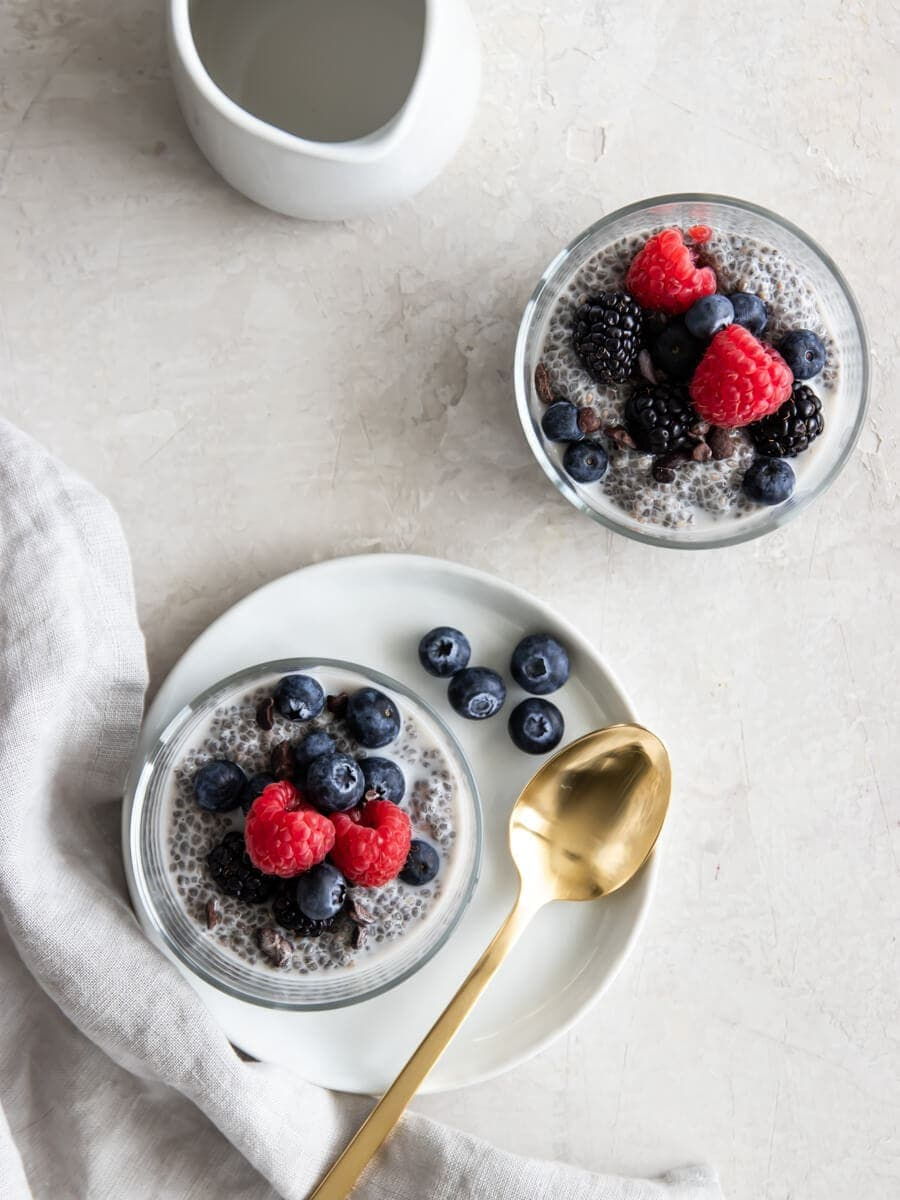 Two cups of vegan chia seed pudding with fresh berries on top