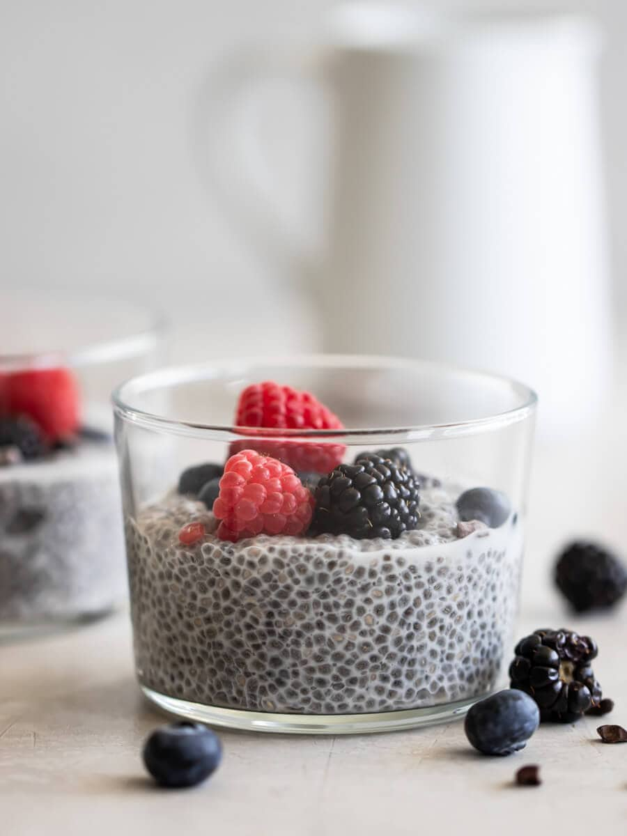 A cup of vegan chia seed pudding with fresh berries on top