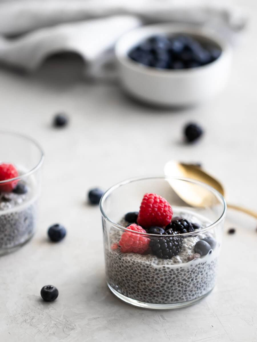 A glass filled with chia seed pudding with fresh berries.