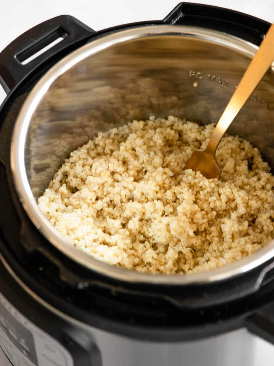 Cooked quinoa in the Instant Pot with a golden fork.
