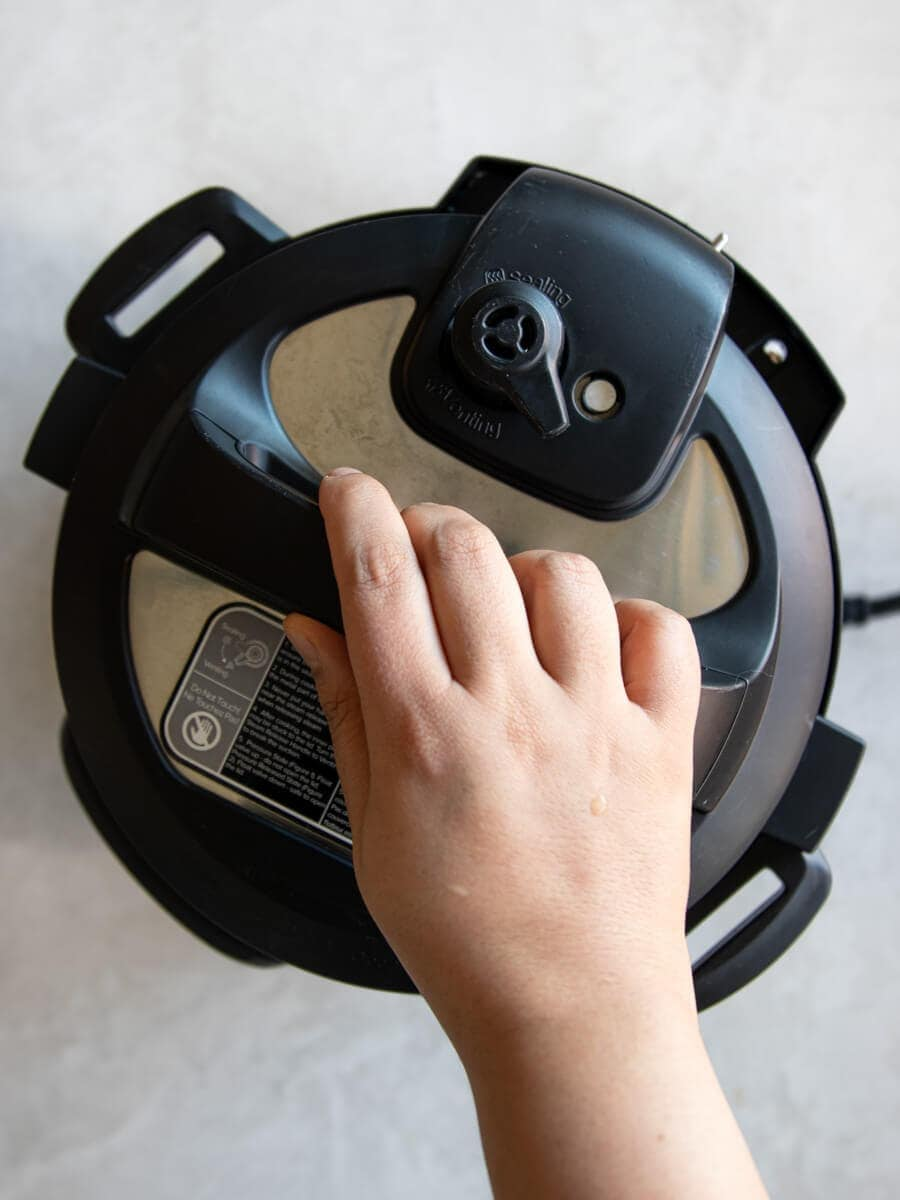Hand closing the Instant Pot.