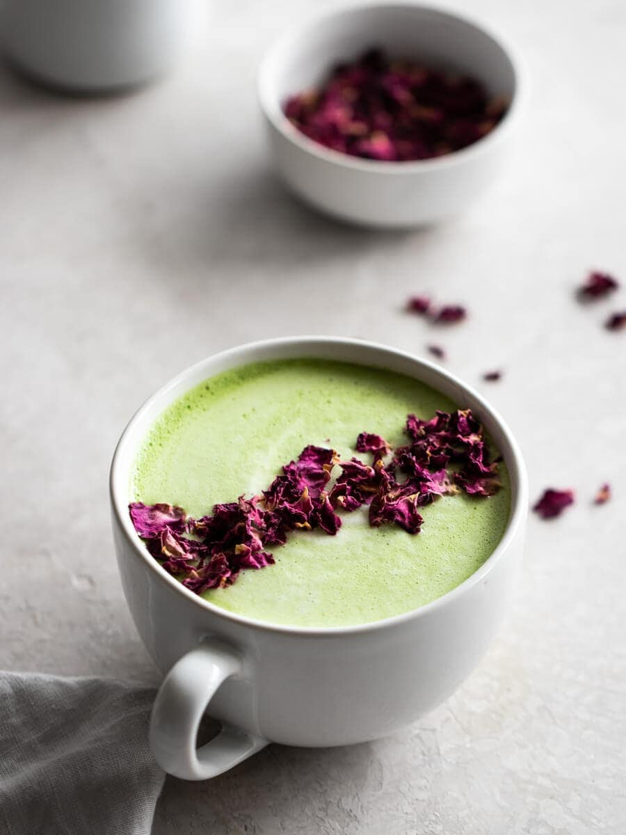 A cup of matcha, sprinkled with dried rose petals. More dried rose petals in the back.