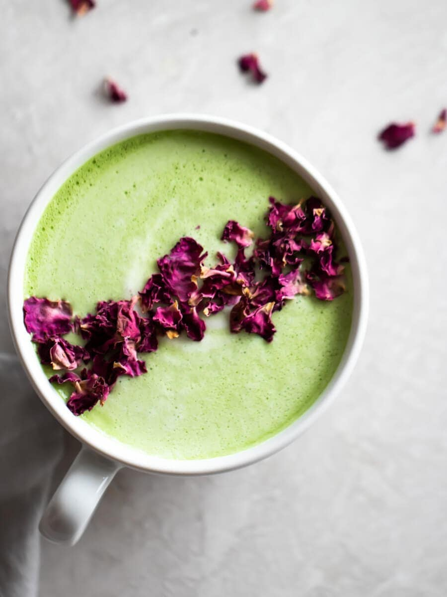 A close-up of a cup of vegan matcha latte, sprinkled with dried rose petals.