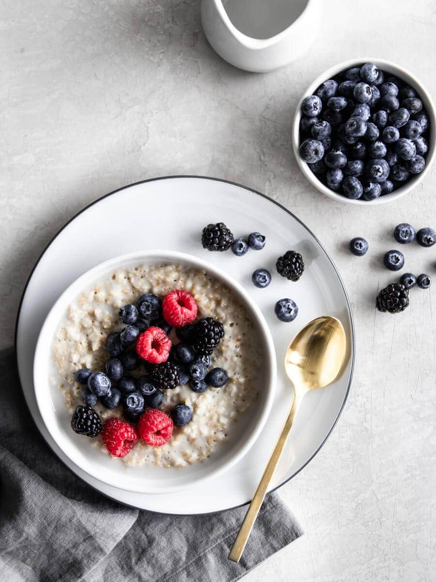 Bowl of overnight steel cut oats with fresh berries on the side.