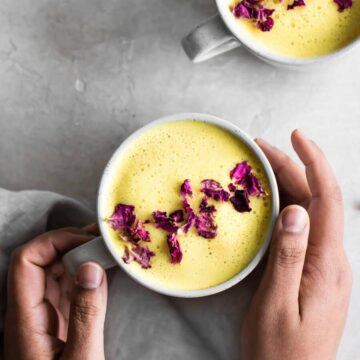 Hands holding cup of turmeric latte