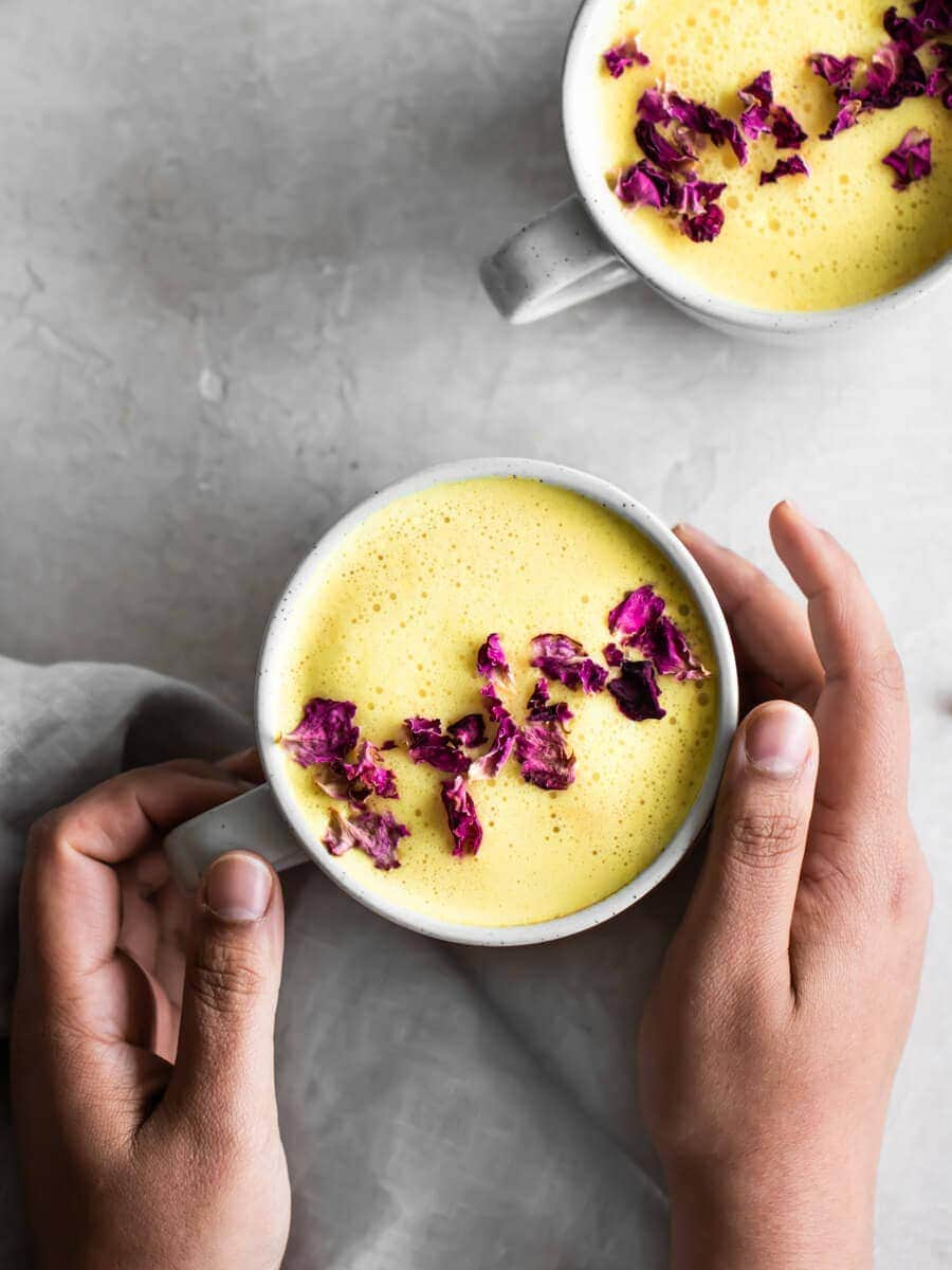 Two hands holding a cup of golden milk, with dried rose petals sprinkled on top.