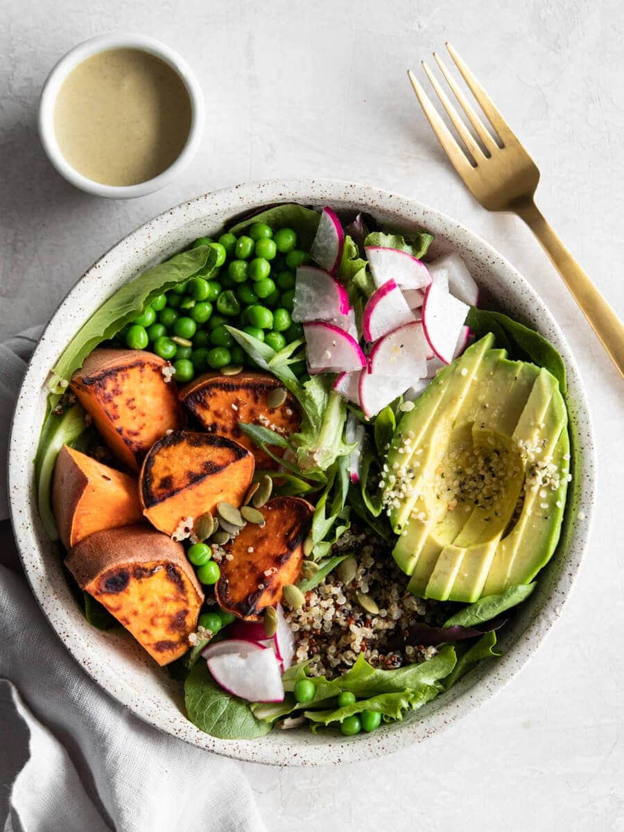 A vegan power bowl filled with roasted sweet potato, avocado, green peas, quinoa, fresh greens, and veggies.