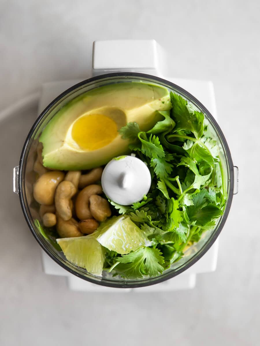 A food processor filled with avocado, fresh cilantro, olive oil, lime, cashews.