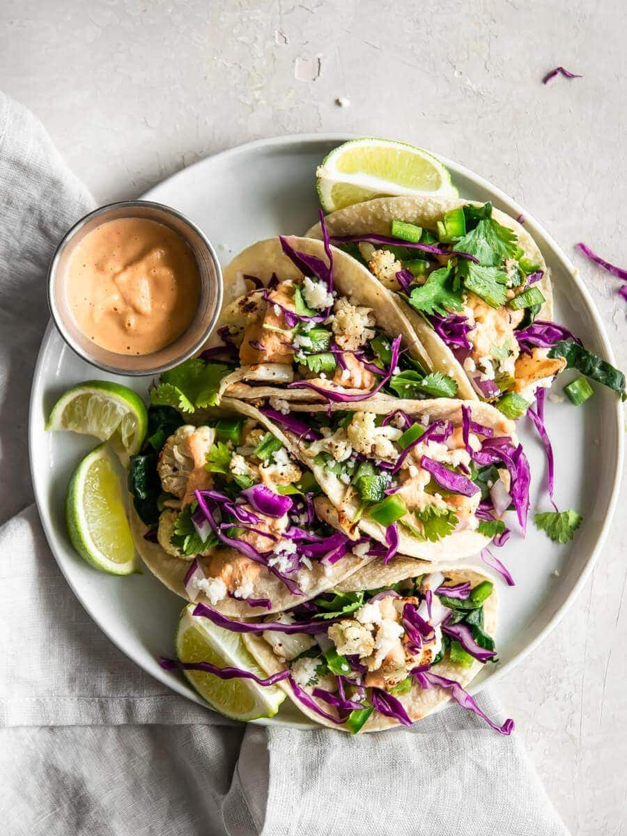 A plate of cauliflower tacos with spicy cashew sauce.