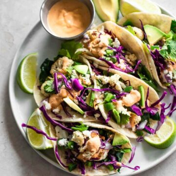 A platter of cauliflower tacos with sauce