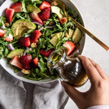 Hand drizzling vinaigrette on strawberry arugula salad