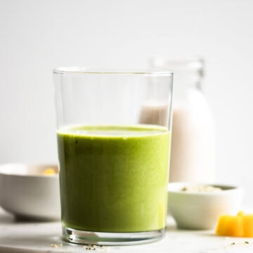 A glass of green smoothie with a bottle of almond milk behind it.