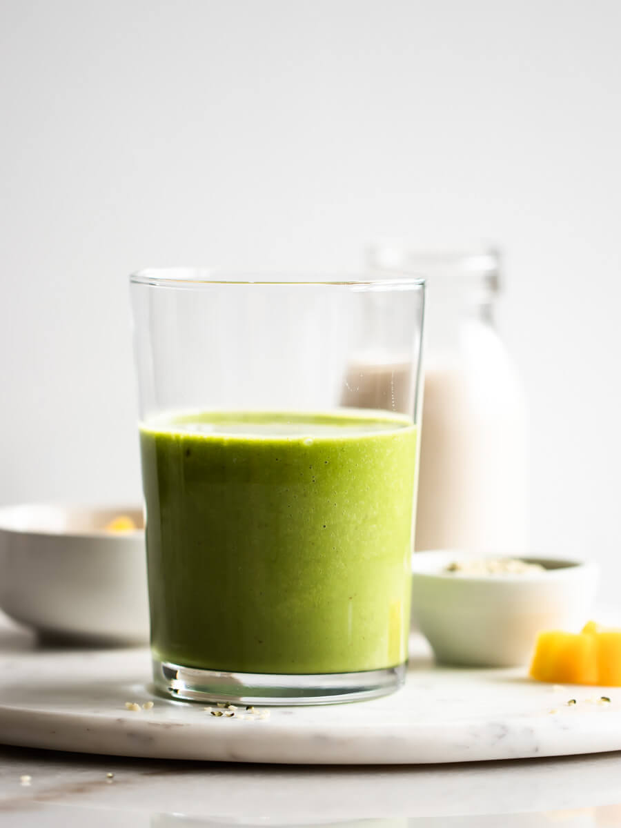 A glass of tropical matcha smoothie with ingredients in the background.