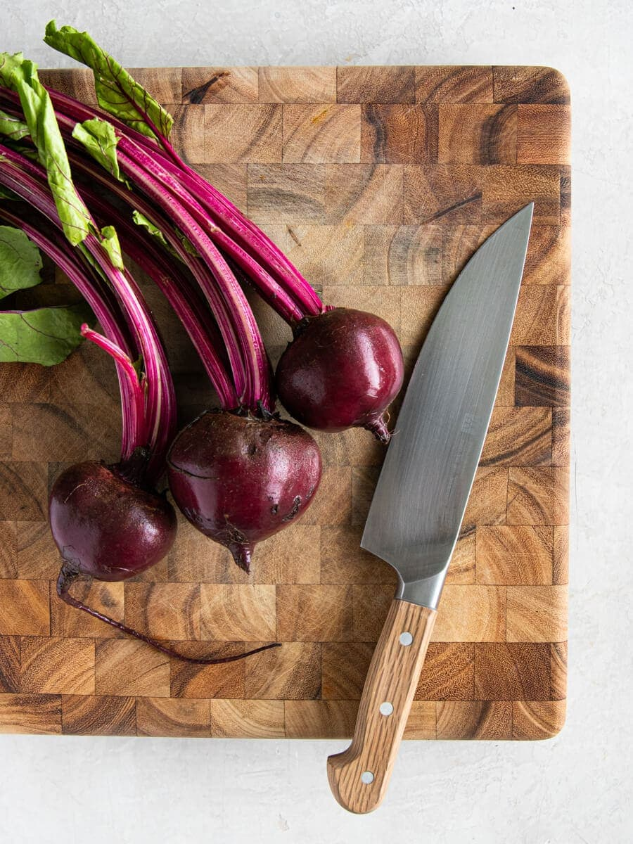 Cleaned beets and a chef's knife on a wooden cutting board.