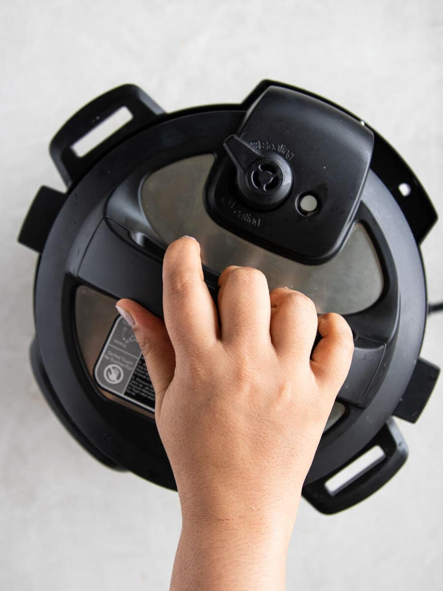 Hand closing the lid of the Instant Pot.