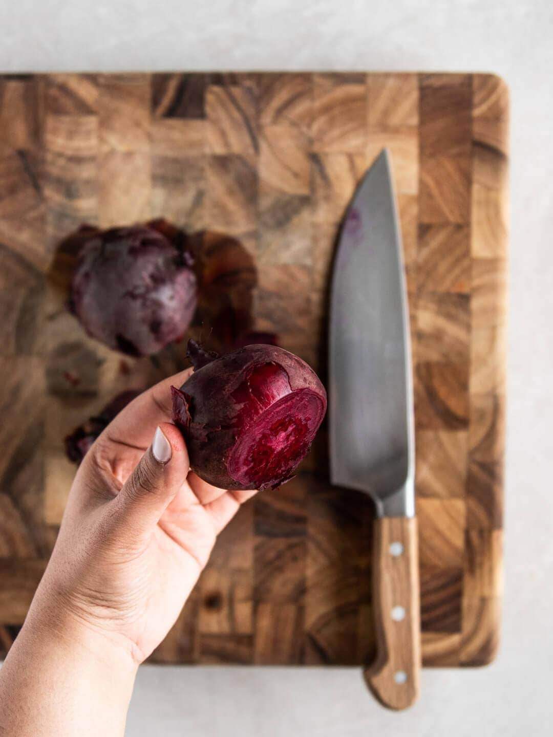 Hands holding cooked beet after slicing off the top.