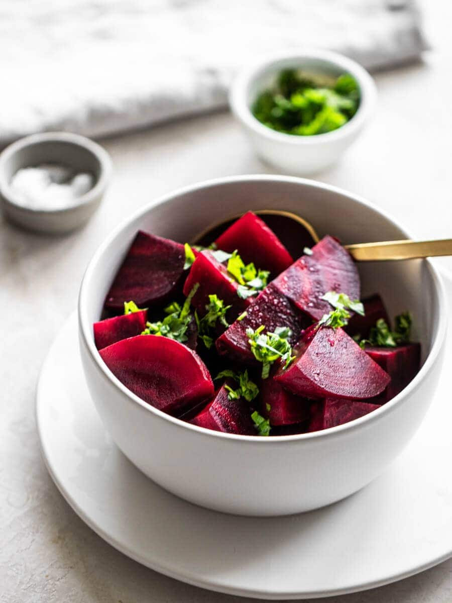 A bowl of cooked beets with a bowl of fresh parsley and another bowl of flaky salt.