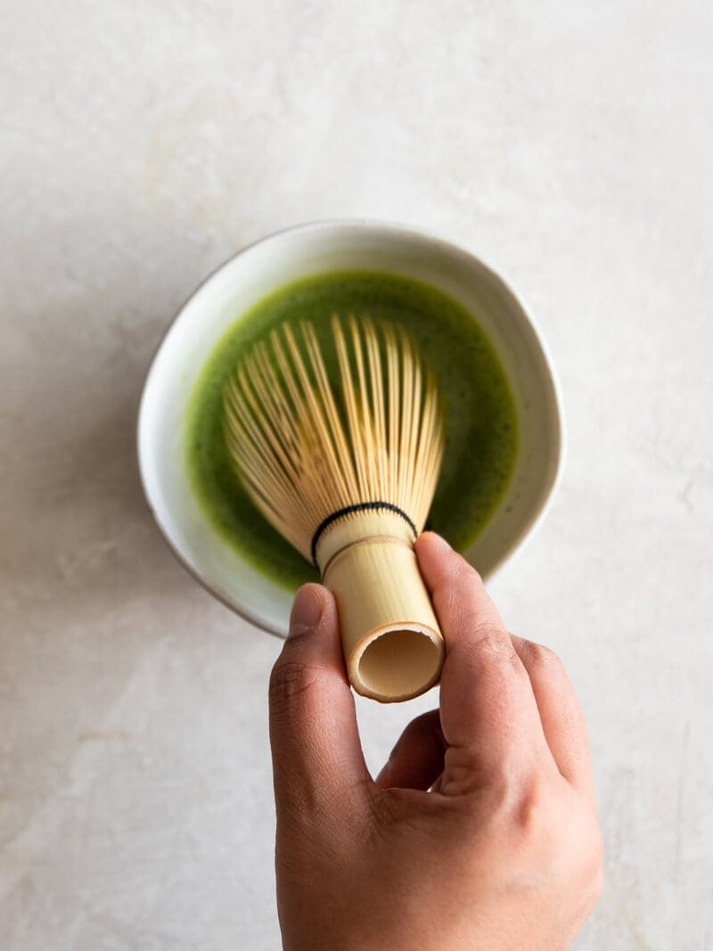 Hand whisking matcha green tea