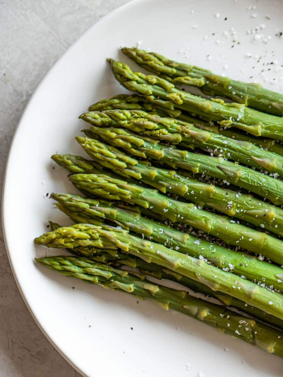 A plate of cooked asparagus topped with flaky salt.