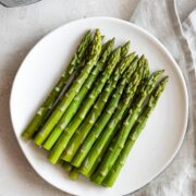 Plate of cooked asparagus with the Instant Pot in the corner.
