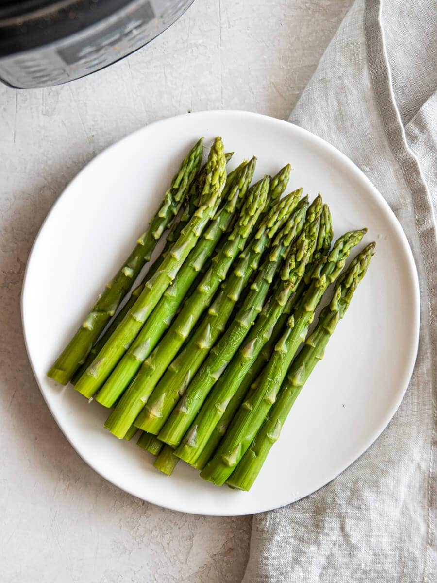 Plate of cooked asparagus with the Instant Pot in the corner
