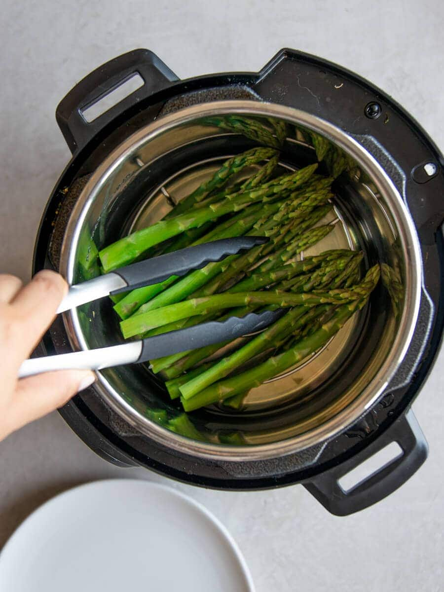 Tongs picking up the cooked asparagus from the Instant Pot