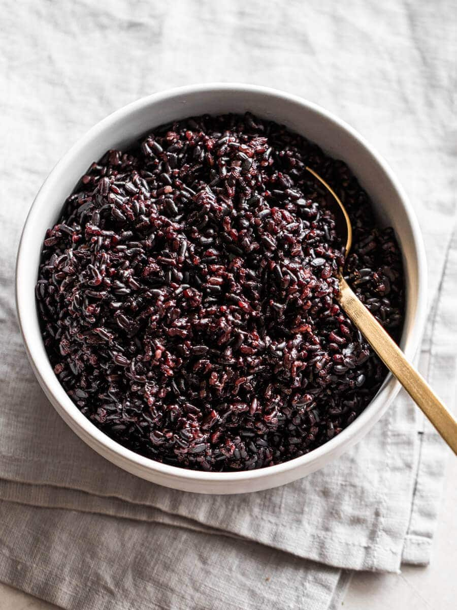 A bowl of black rice with a spoon in it