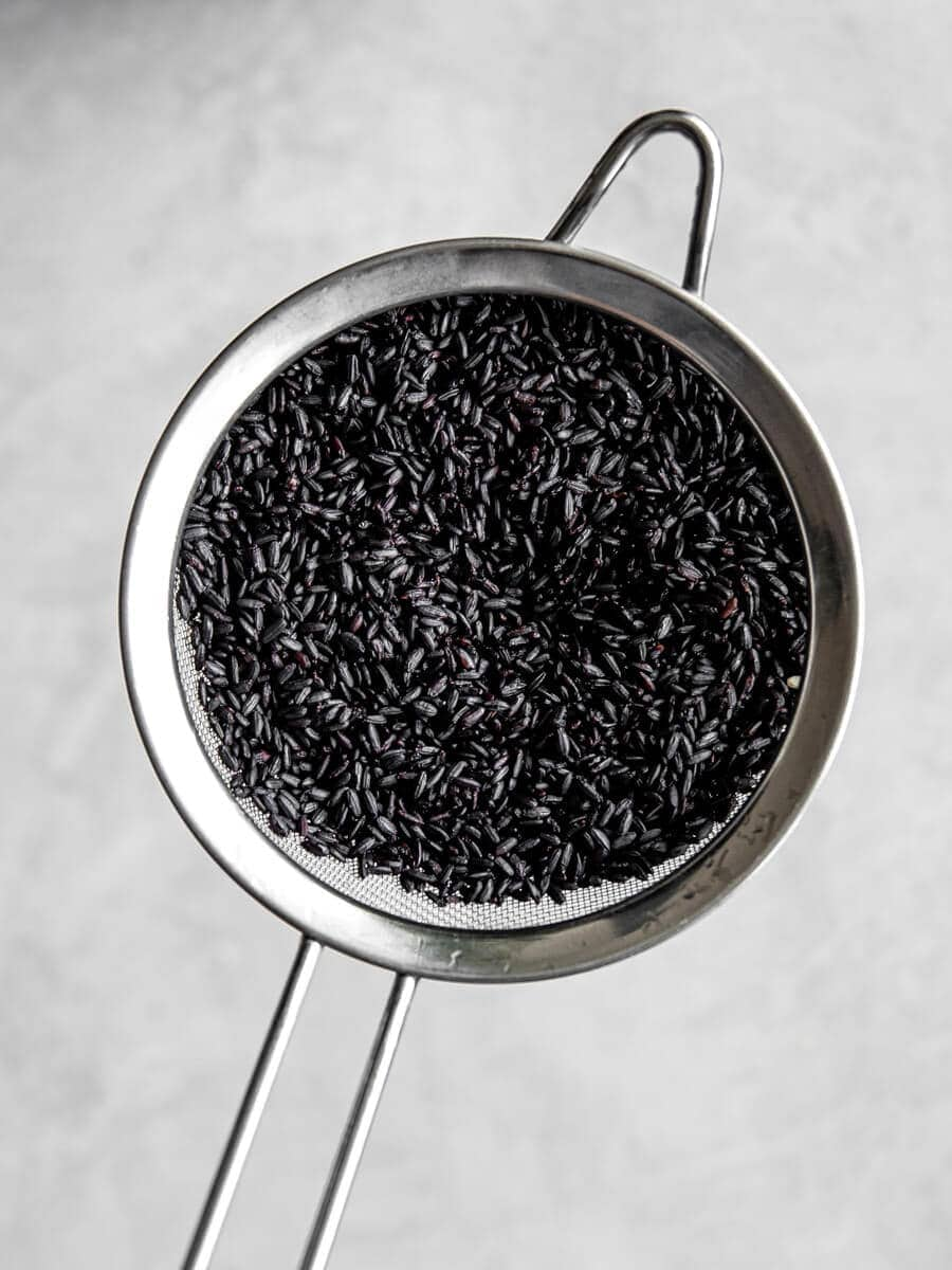 Mesh sieve filled with black rice