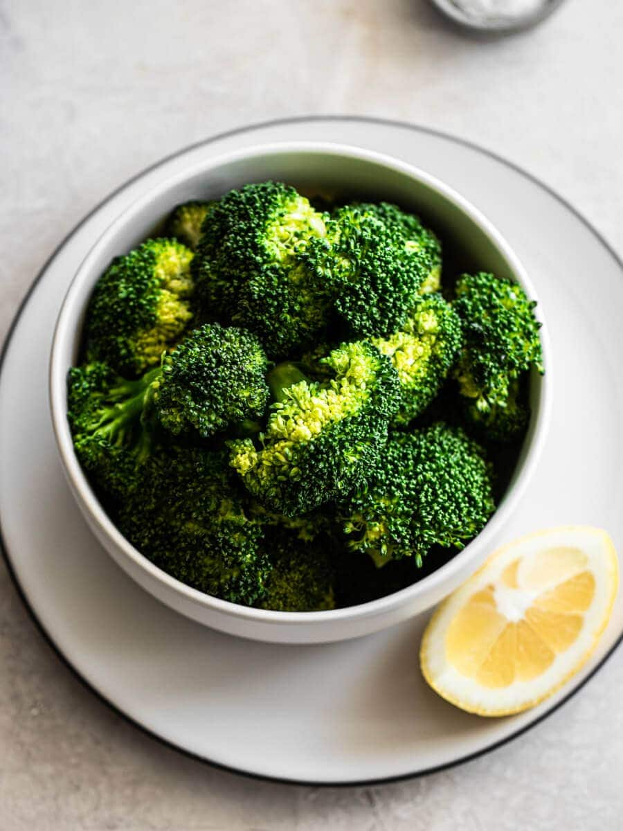 A bowl of cooked broccoli with a lemon wedge