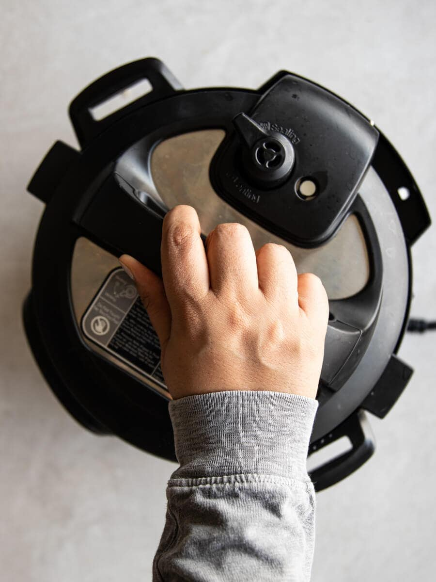 Hand closing lid of instant pot