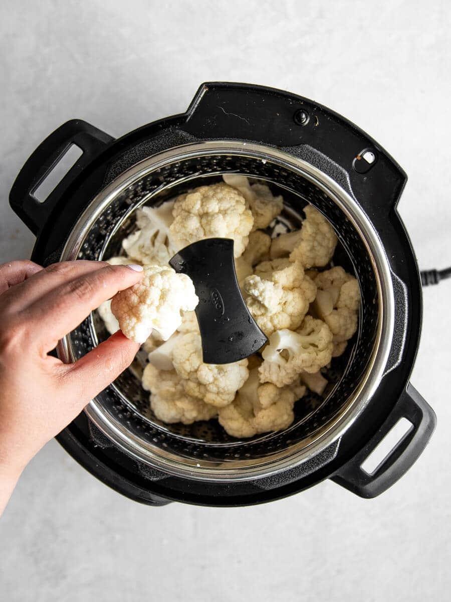 Hand placing cauliflower florets on steamer basket.
