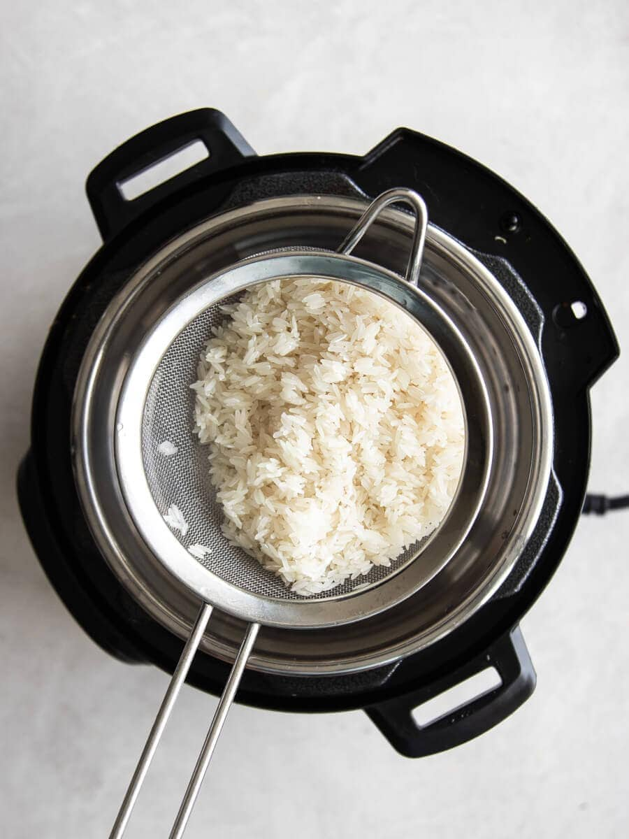 Mesh sieve with rinse jasmine rice sitting on the Instant Pot